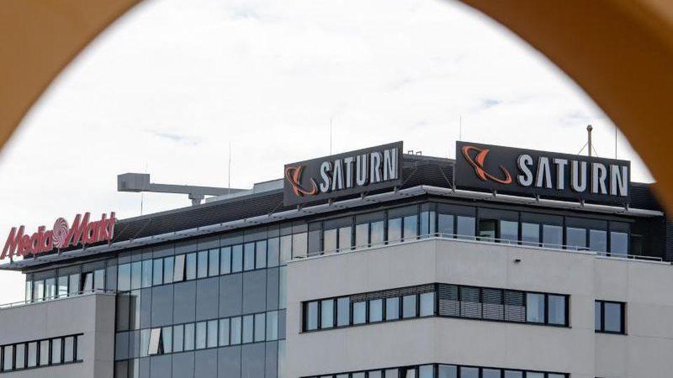Ein Schild mit den Schriftzügen von Media Markt und Saturn sind an der Firmenzentrale zu sehen. Foto: Armin Weigel/Archiv