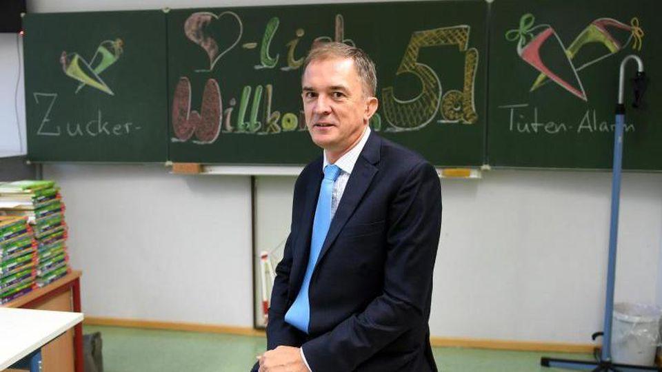 Marco Tullner (CDU) sitzt in einem Klassenraum auf einem Tisch. Foto: Hendrik Schmidt/Archiv